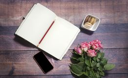 Top view of blank sheet of notebook and red and pink roses flowers on rustic brown wooden table. Copy space. Royalty Free Stock Photos