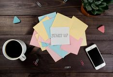 Flat lay, top view office table desk. Workspace with blank clip board, pencil, green leaf, and coffee cup on dark background. Flat lay, top view office table stock photos