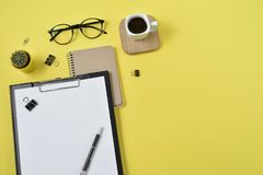 Flat lay, top view office table desk. Workspace with blank clip board, office supplies, pen, cactus, coffee cup on a wooden stand stock image