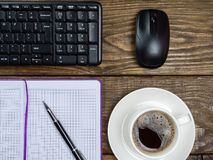 Flat lay, top view office table desk. Workspace with blank note book, keyboard, office supplies and coffee cup on wooden. Background royalty free stock image