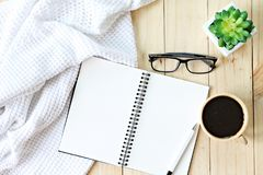 Flat lay or top view of white knitted blanket, eyeglasses, cup of coffee and blank notebook paper on wooden background Royalty Free Stock Images