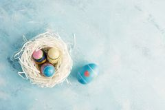 Flat lay top view white paper nest with three vintage Easter eggs and one blue egg with red heart on blue background Stock Photo