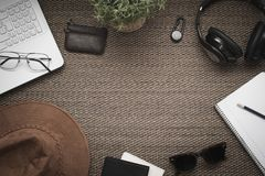 Flat lay. Top view of workspace. Travel or trip planning. Laptop mobile phone, wallet, hat, headphones, notebook, pencil royalty free stock images
