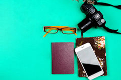Flat lay travel concept with camera, mobile phone on green backg Royalty Free Stock Photography
