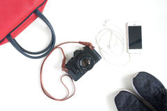 Flat lay of travel items with film camera, smartphone, red hand Stock Photography