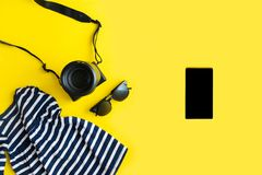 Flat lay traveler accessories on yellow background with blue dress, camera and sunglasses. Summer background concept royalty free stock photography