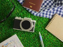 Flat lay traveling accessories on green grasses background with copy space stock photo