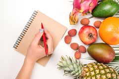 Flat Lay with tropical fruit and notebook. Woman hand writes diet plan. Stylish workplace. Diet, healthy lifestyle and fitness stock image