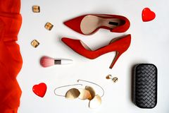 Flat lay tValentines day party outfit composition red shoes accessories jewelry clutch two hearts on white background. Party date stock photos