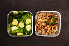 Flat lay of two containers with vegetables and mushrooms on a black wooden background, closeup stock photos