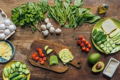 Flat lay with various arranged healthy vegetables, mushrooms and raw chicken eggs for cooking breakfast. On wooden tabletop stock photography