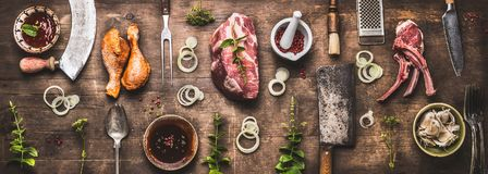 Flat lay of various grill and bbq meat : chicken legs, steaks, lamb ribs with vintage kitchenware kitchen utensils. Meat Fork and Butcher Cleaver and herbs stock photography