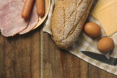 Flat lay of various ingredients for breakfast on wood background, bread, egg, sausage, ham, and cheese stock photo