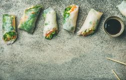 Flat-lay of vegan spring or summer rice paper rolls. Helathy Asian cuisine. Flat-lay of vegan spring or summer rice paper rolls with vegetables, sauce and Stock Photo