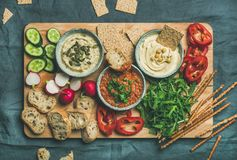 Flat-lay of Vegetarian dips hummus, babaganush, muhammara on wooden board Stock Images