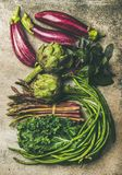 Flat-lay of fresh green and purple vegetables. Flat-lay veriety of green and purple vegetables over concrete background, top view. Local seasonal produce for Royalty Free Stock Photos