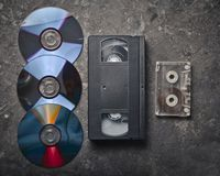 Flat lay video cassettes, CD's, audio cassette on a black concrete surface. Retro media technology of the past. Top view Royalty Free Stock Image