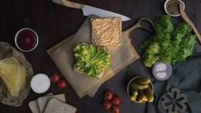 Flat lay video of the chef's hand finalizes sandwich with salad and cheese on the wooden board in the beam of light