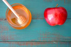 Flat lay view of honey jar and red apple on a turquoise backgrou Royalty Free Stock Photo
