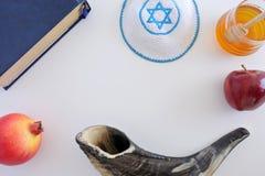 Flat lay view of Shofar, Torah book, Kippa, apple, honey and Pom Royalty Free Stock Photos