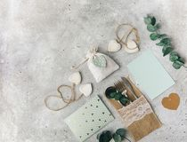 Flat lay wedding composition with card, decorations and eucalyptus, greetings, invitation. Vintage shabby chic style Stock Photos