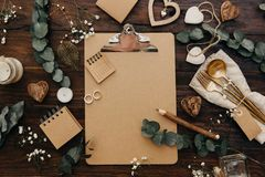 Flat lay Wedding planning. Craft clipboard with rustic decorations on wooden background. Vintage Greenery Wedding Details royalty free stock photography
