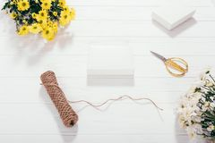 Flat lay white blank present boxes next to bouquets. Of yellow flowers, gold scissors and twine. Process of handmade packaging of gifts for the holiday on royalty free stock photos