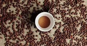 Coffee beans and cup of powder. Flat lay of white cup with ground coffee powder on canvas textile with roasted coffee beans around stock video footage