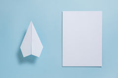 Flat lay of white paper plane and blank paper on pastel blue col stock image