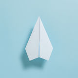 Flat lay of white paper plane on pastel blue color background royalty free stock image