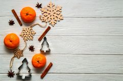 Flat lay. White rustic table with tangerines, cinnamon sticks, anise-star, Christmas molds for pastry,wooden snowflakes. royalty free stock images