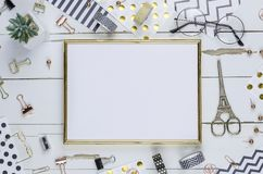 Flat lay, white wooden desk and golden frame. Gold stapler, stripe gold pattern, pencil. View top. Table up. Mock-up royalty free stock photo