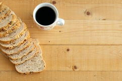 Flat lay of whole wheat bread and and coffee on wooden table. royalty free stock photography