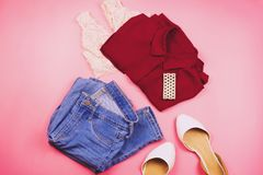 Flat lay of woman clothes with purple shirt,blue jeans, bralette, bracelet and flats.  Stock Images