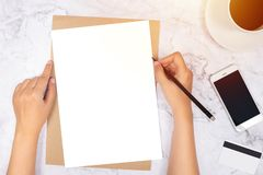 Flat lay of woman hand writing in a blank white paper on brown paper envelope with pencil ,mobile phone , credit card. And black coffee on white marble stock image