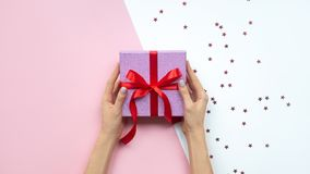 Woman hands holding gift with bow on pink and white background with copy space. Flat lay. stock images