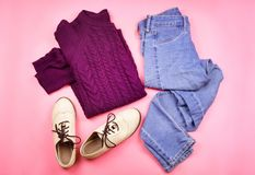 Flat lay of woman`s autumn cozy clothes. Pink background Stock Photos