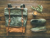 Flat-lay of woman`s fall accessories and coffee. Haki suede leather oxford boots, large green backpack and cup of espresso over wooden background, top view stock photo