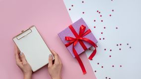 Flat lay. Woman`s hands paper. To-do list. Christmas ideas, notes, goals or plan writing concept. Valentine`s Day. stock photo