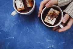 Flat lay of woman`s hands in sweater and two cups of cocoa or hot chocolate