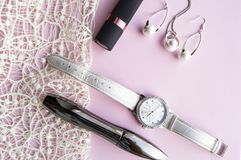 Flat lay women`s accessories collage with stylish watches, earrings and pendant with white pearls, lipstick, mascara on a Lacy. Pink background royalty free stock images