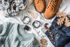 Flat lay women`s clothing for autumn walks, top view. Brown suede boots, jeans, a blue pullover, scarf, bracelets, watches, headp. Hones, perfume on a light Stock Images