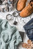 Flat lay women`s clothing for autumn walks, top view. Brown suede boots, jeans, a blue pullover, scarf, bracelets, watches, headp Stock Photography