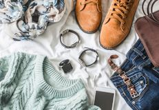 Flat lay women`s clothing for autumn walks, top view. Brown suede boots, jeans, a blue pullover, scarf, bracelets, watches, headp. Hones, perfume and bag on a stock photos