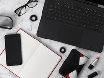 Flat lay workspace with laptop, planner, glasses, mobile phone, ear rings, hair tie, comb and lipstick royalty free stock images