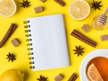 Flat lay on the yellow bright background Black tea Lemon Cinnamon Star Anise brown sugar jar of Honey Notepad for text. Flat lay on the yellow bright background Stock Image