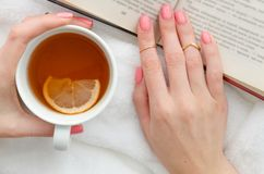 Flat lay young woman reading a book and holding cup of tea with lemon. royalty free stock photos