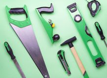 Flat layout: a set of hand tools for construction and repair on a green background. Top view stock photography