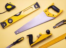 Flat layout: a set of hand tools for construction and repair on a yellow background. Top view stock image