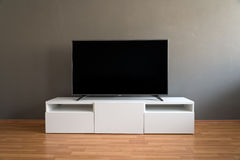 Flat LCD television on white cabinet in the living room. With dark gray wall and parquet floor Royalty Free Stock Images